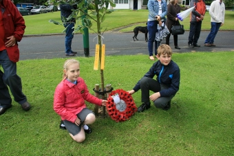 Pupils lay wreath at tree